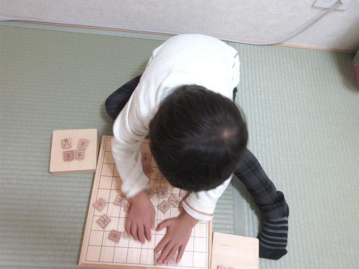 将棋盤をぐちゃぐちゃにする子供