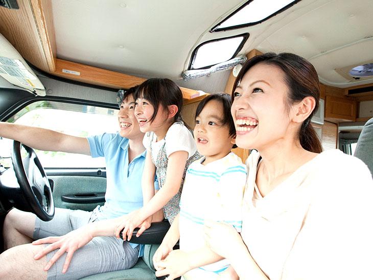 広い車の中の喜ぶ家族