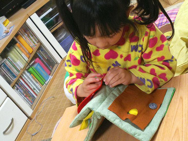 布絵本のボタン付けをする幼児