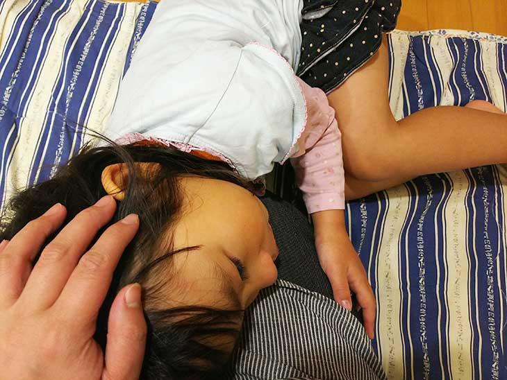 腹痛で母親に膝枕をしてもらっている女の子