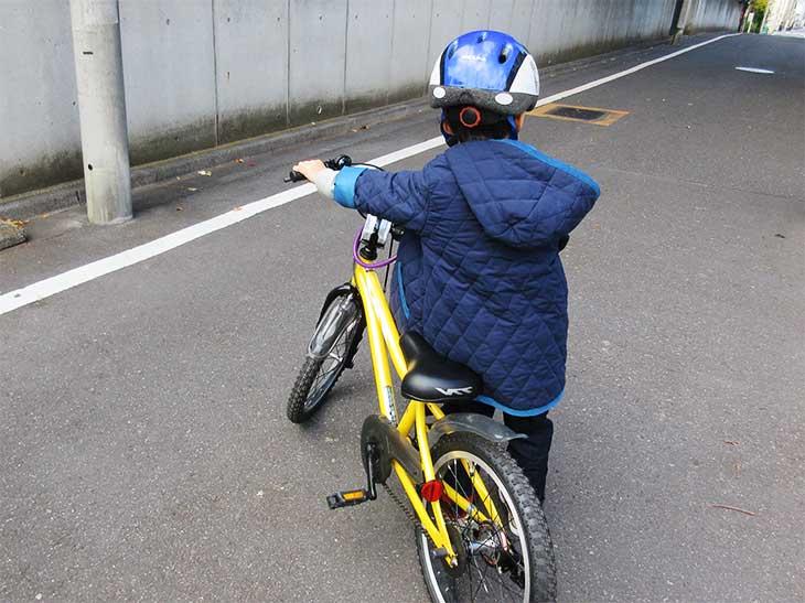 自転車を押してる男の子
