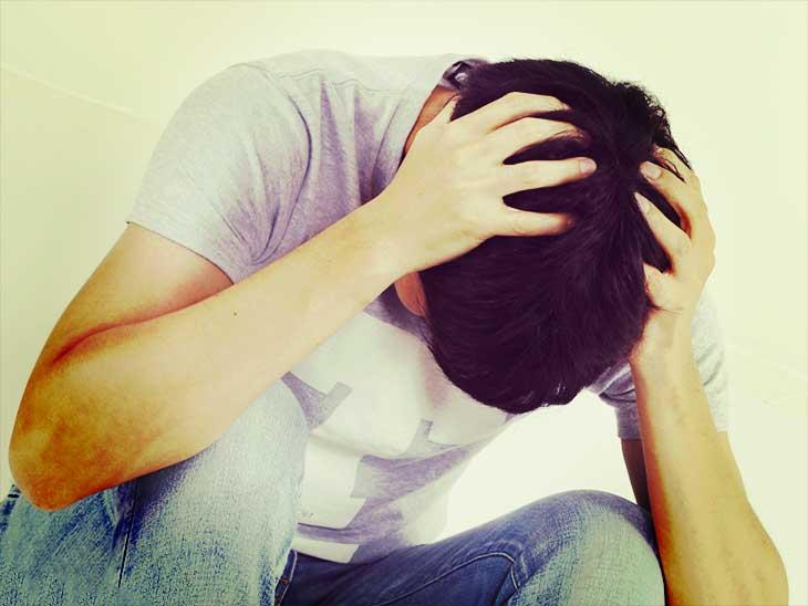 頭を抱えて悩んでいる男性