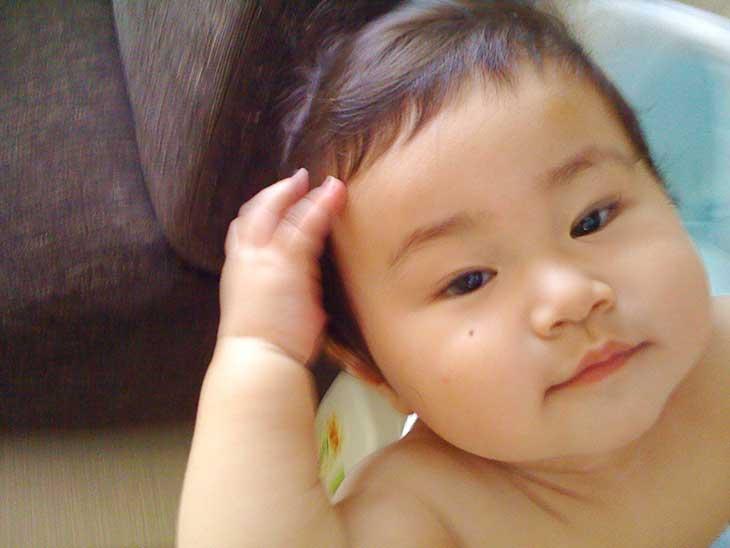 髪をかき上げる赤ちゃん