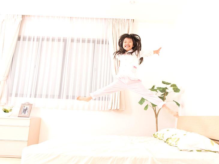 ベッドでジャンプをする子供
