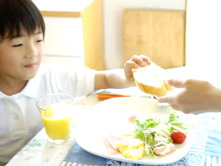 朝ごはんを食べさせる母親の手