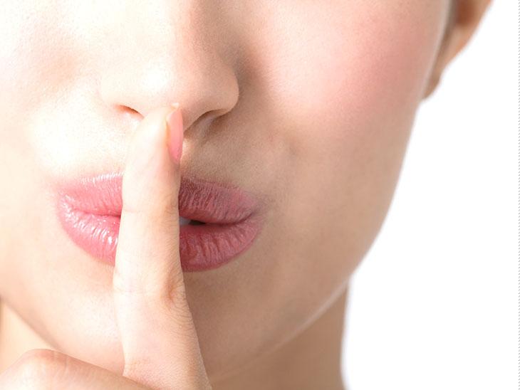 口に人差し指をあてて静かにするよう訴えてる女性