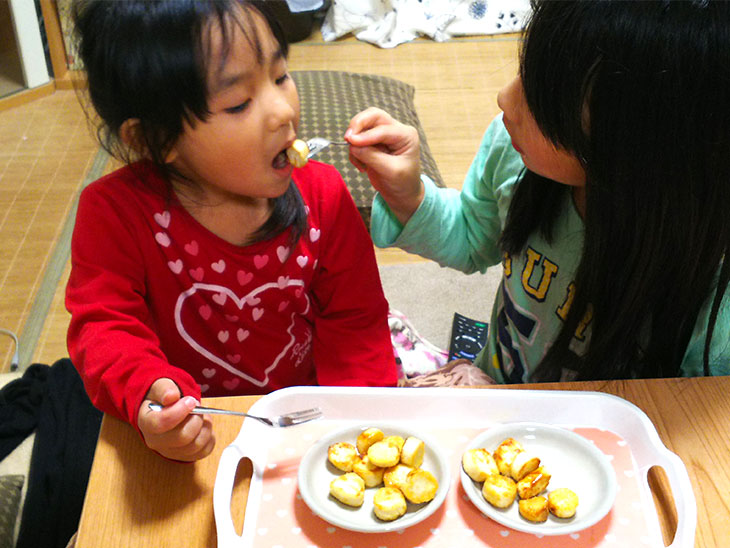 家で作った給食のおやつを食べる姉妹