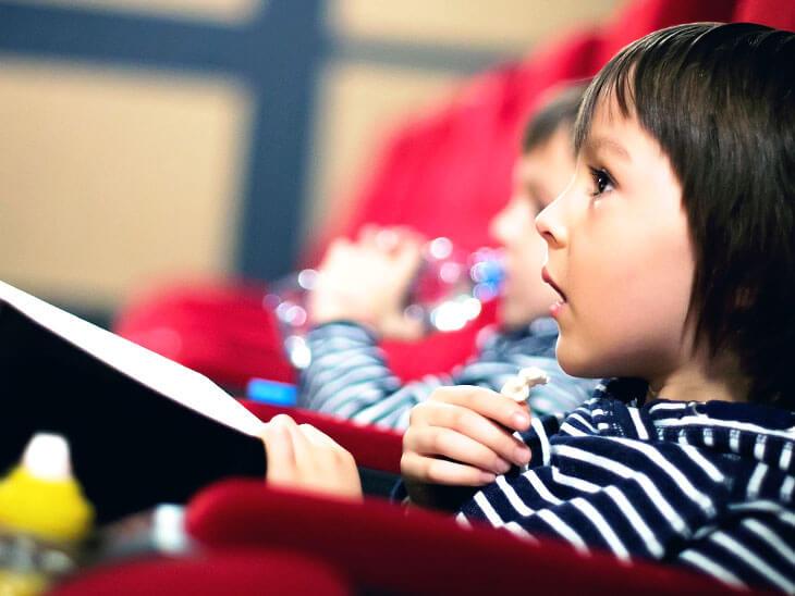 映画館で映画を見る子供
