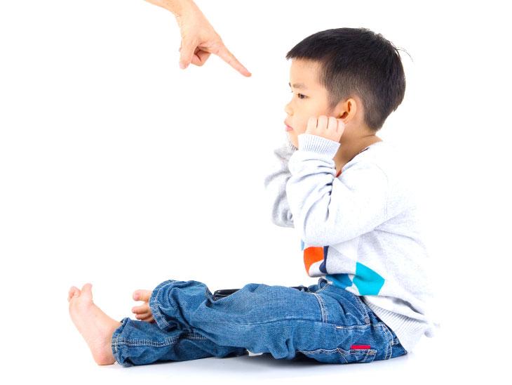 子供に指を指す大人の手