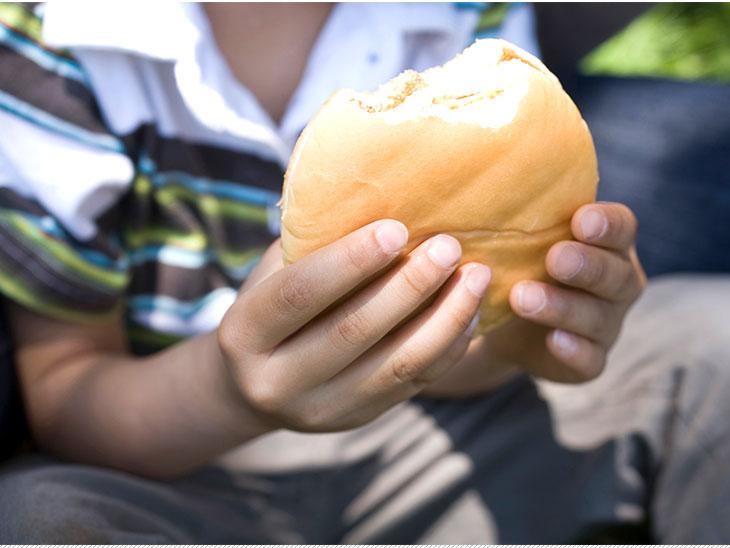 ハンバーガーを食べる子供の手