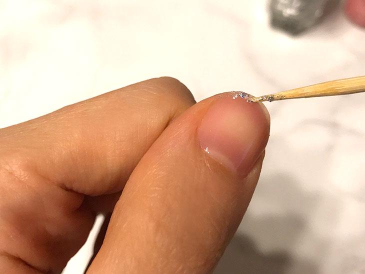 竹串を使って先端にラメネイルを塗る様子