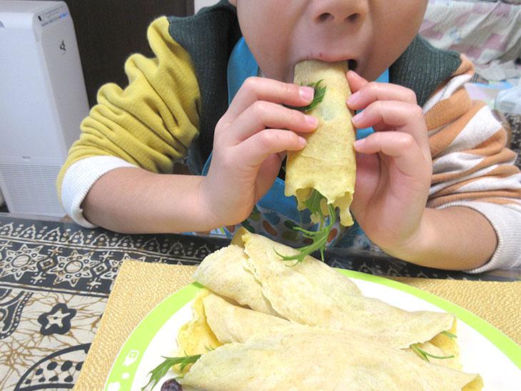 親子で作った料理を食べる子供