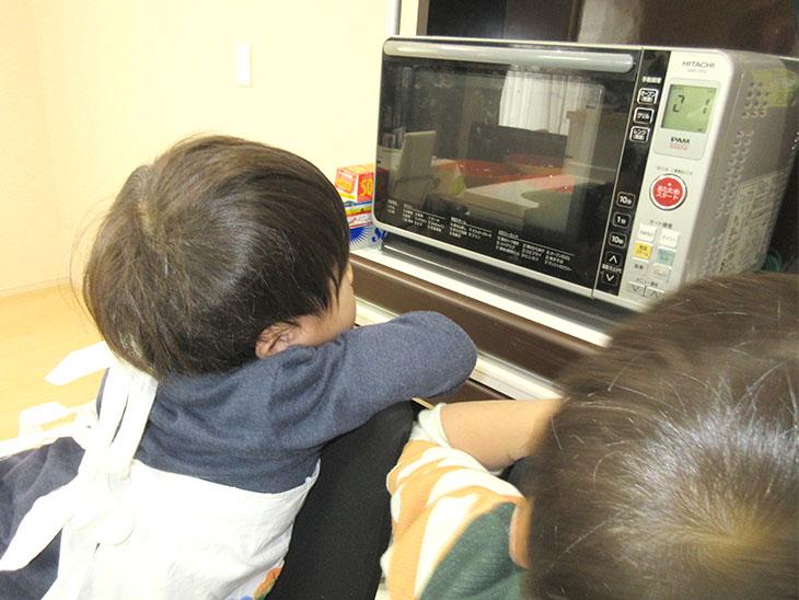 電子レンジの前で出来上がりを待つ子供