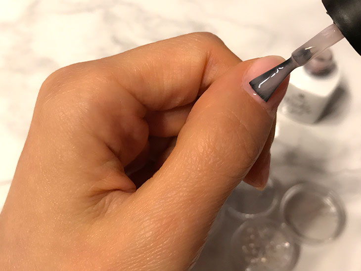爪にジェルネイルを塗る様子