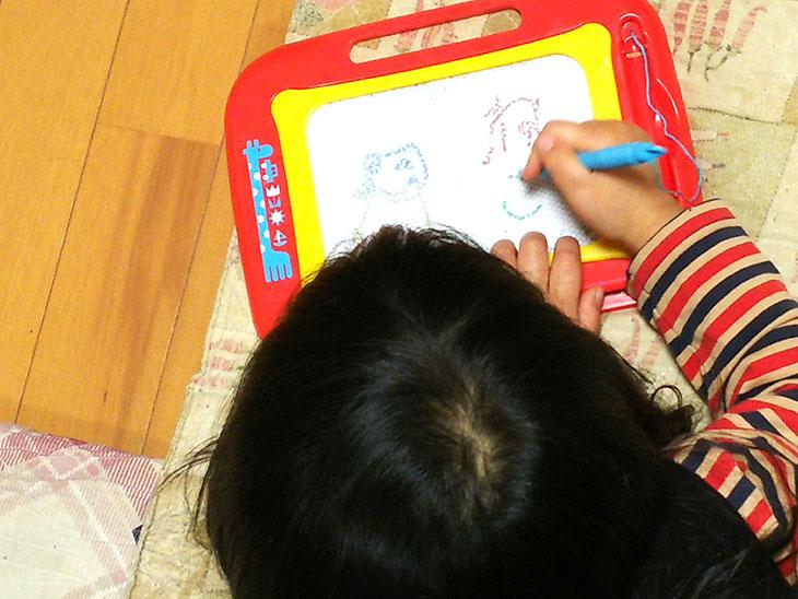 遊びながら字を書く練習をする幼児