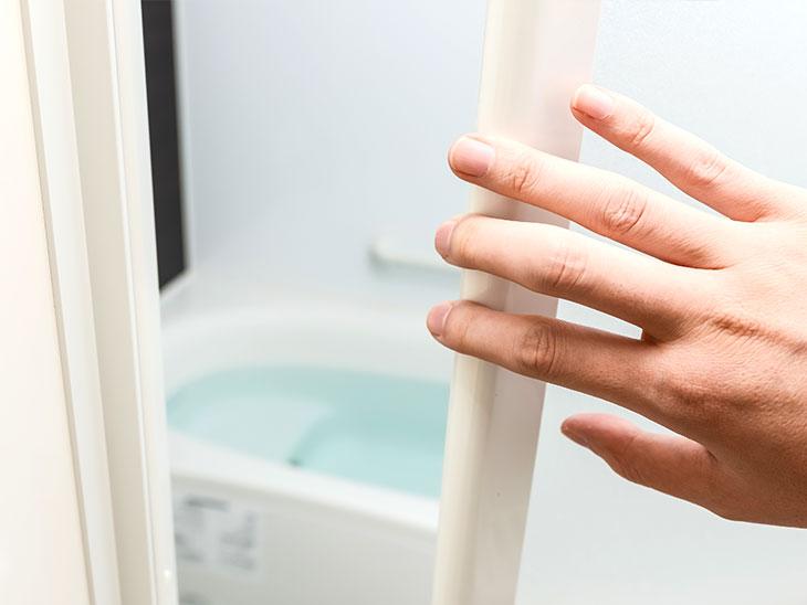 お風呂場へのドアを開ける人の手