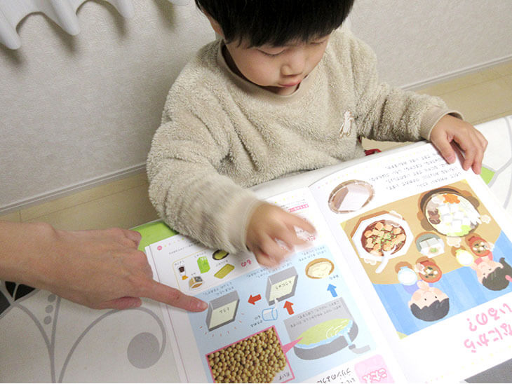 子供の疑問を図鑑で調べる親子