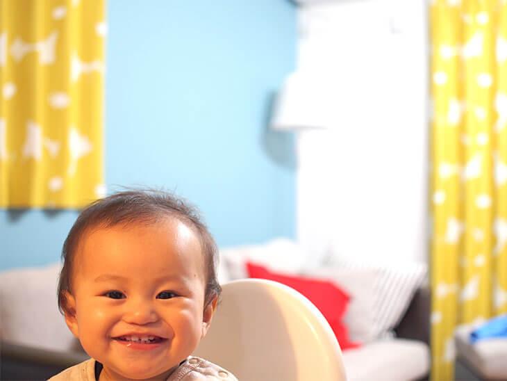 壁紙ペイントした部屋で笑う赤ちゃん