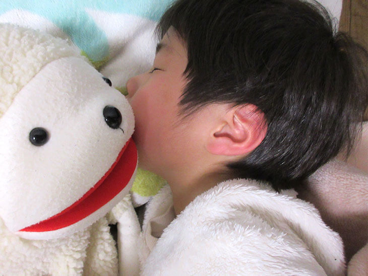 ぬいぐるみと寝る子供