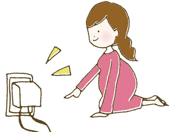 コンセントカバーをつける妊婦