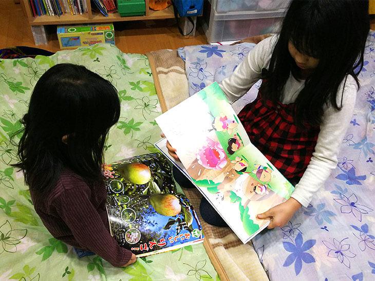 食育絵本を読む幼児と小学生