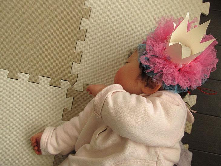 頭に紙コップの王冠をつけた赤ちゃん