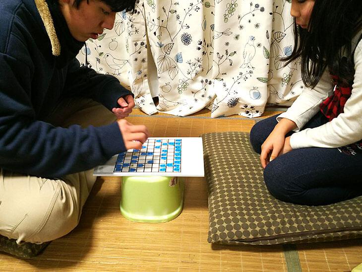 手作りした将棋で遊ぶ子供