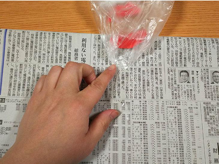 中の新聞紙をビニール袋にとめる様子