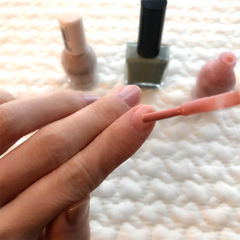 人差し指の爪にピンク色のネイルを塗っている様子