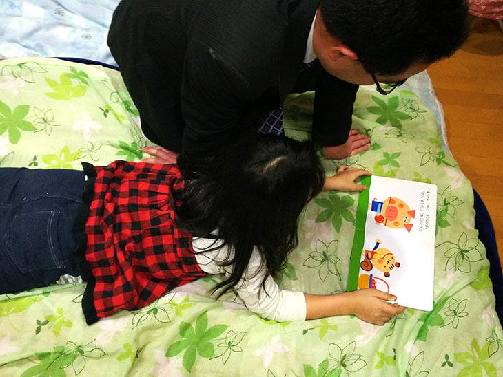 寝る前に読み聞かせをする父親