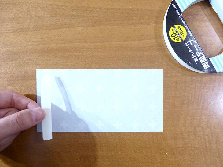 半分の折り紙の端に両面テープを貼っている様子