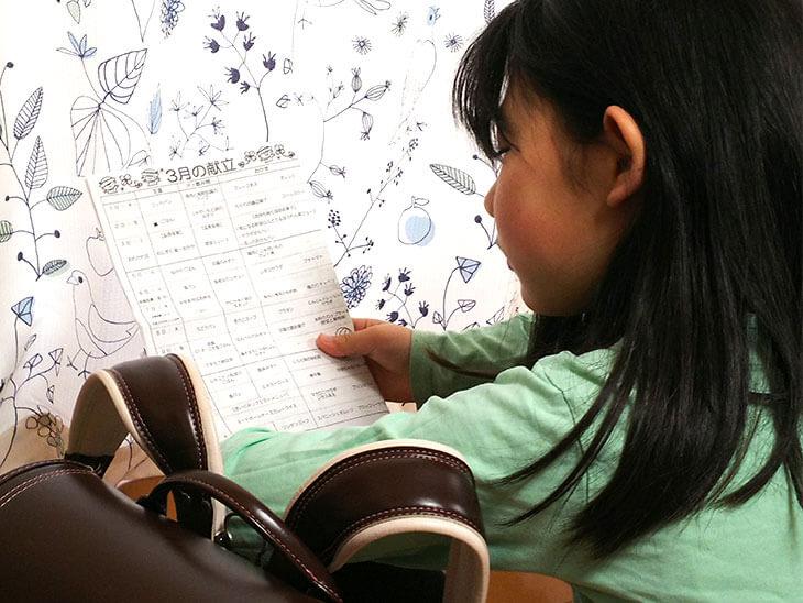 献立表を見る小学生の女の子