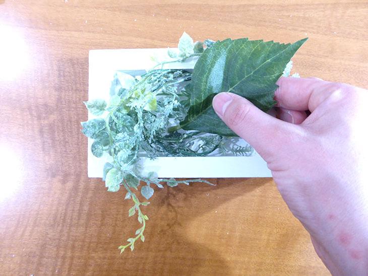 フレーム内に造花の葉を入れる様子