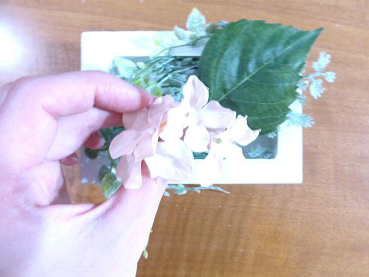 葉の上に造花を飾る様子