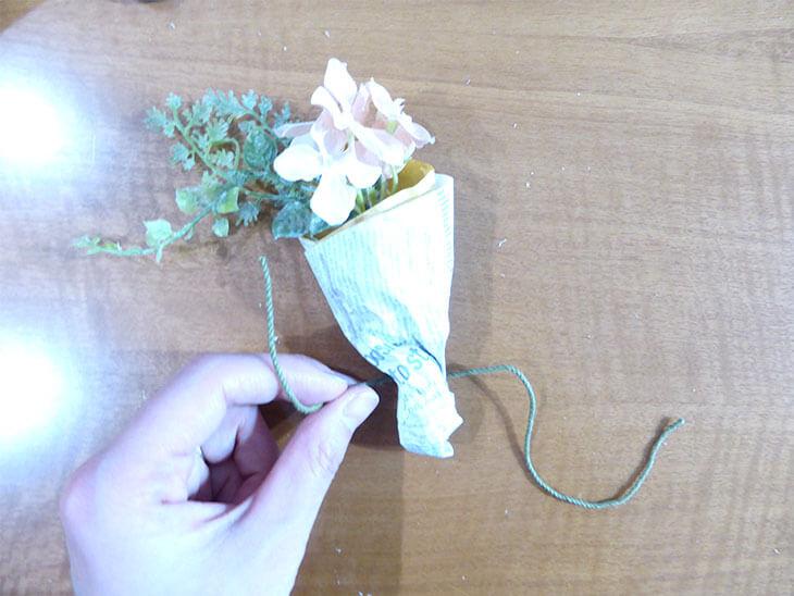 包んだ折り紙の上をひもで結んだブーケ