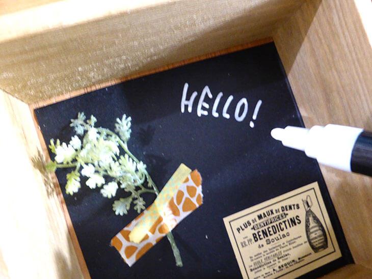 ウッドボックスの底に文字を書き込む様子