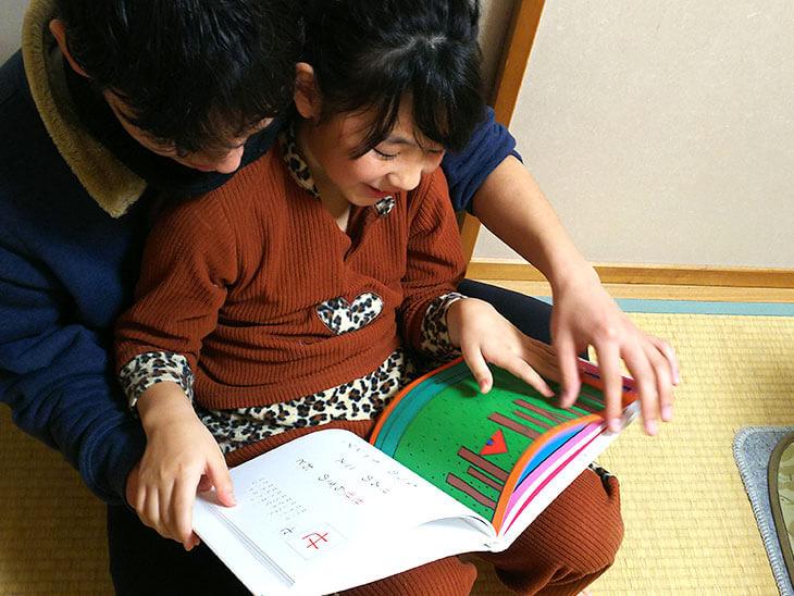 膝の上で絵本を読んでもらう子供