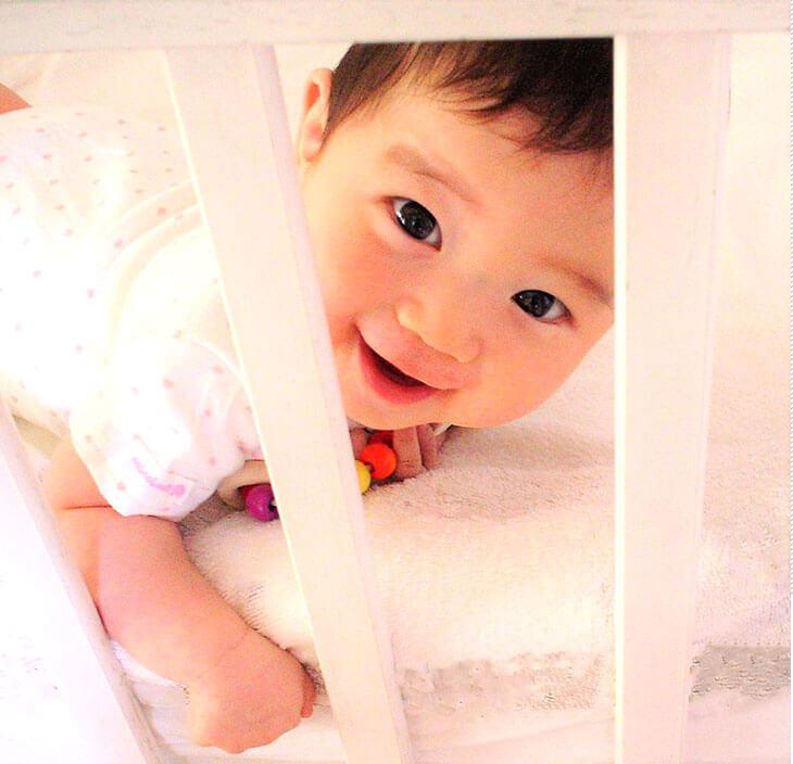 ベビーベッドから見た赤ちゃんの楽しい表情