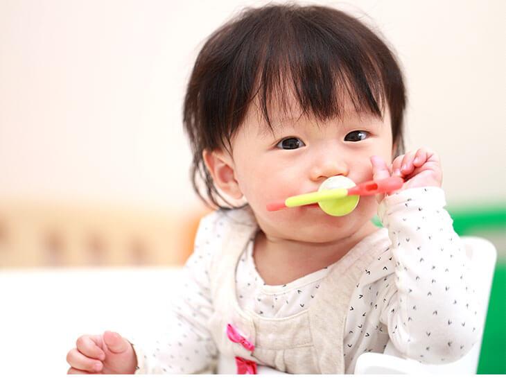 おもちゃを口に入れた赤ちゃん