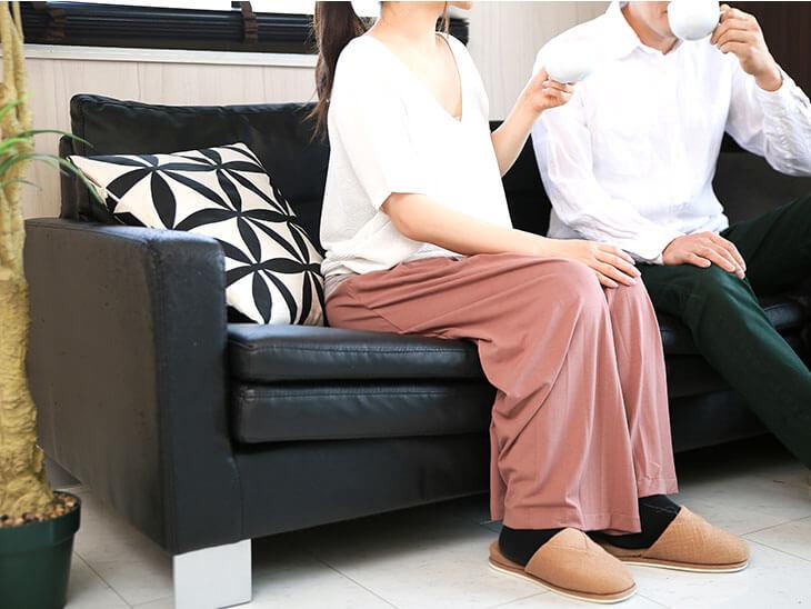 ソファに座ってコーヒーを飲む夫婦