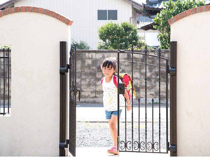 自宅の門に1人で入る下校時の小学生の鍵っ子の女の子