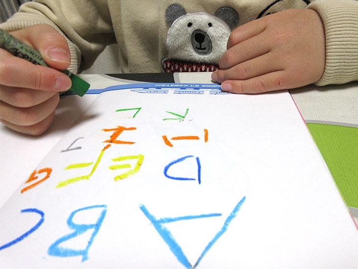 進んでアルファベットと書く子供