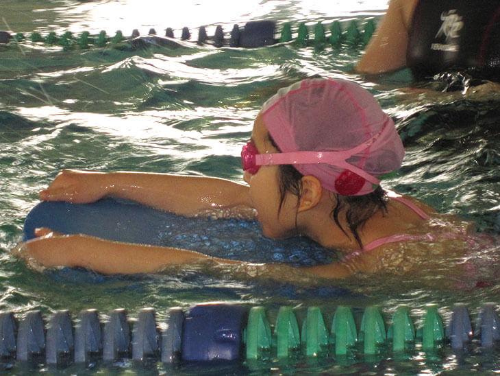 スイミング教室で泳ぐ女の子