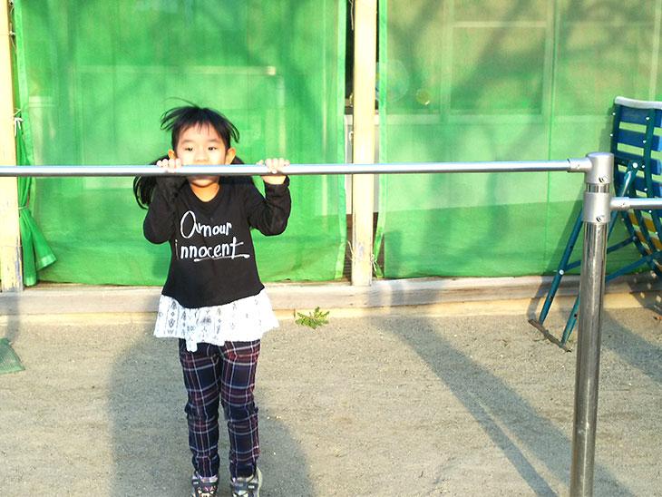 鉄棒の練習をする女の子の幼児