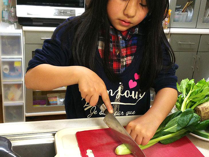 小学生が野菜を切る様子