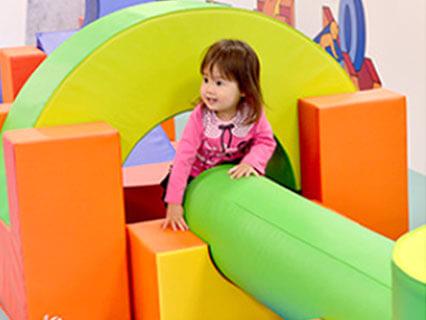 室内遊び場でソフトブロックで遊ぶ女の子