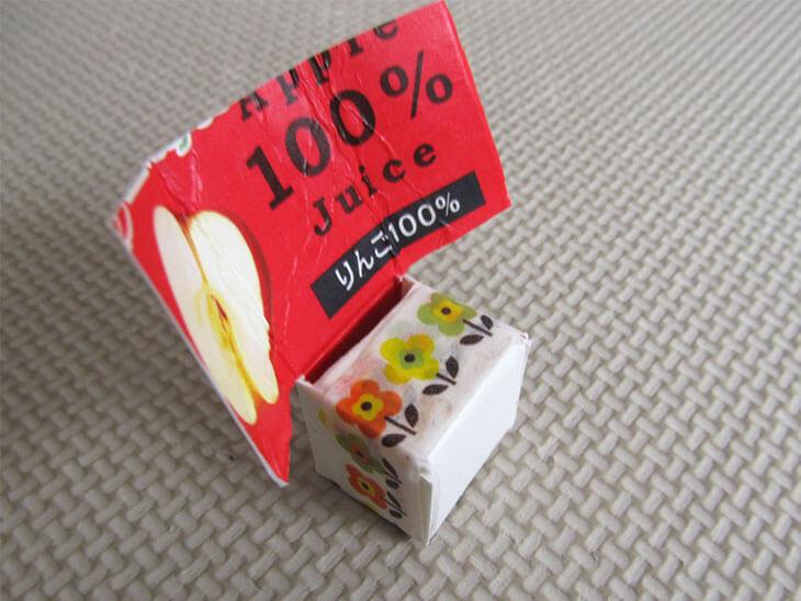 箱型になった牛乳パックをテープで留める様子