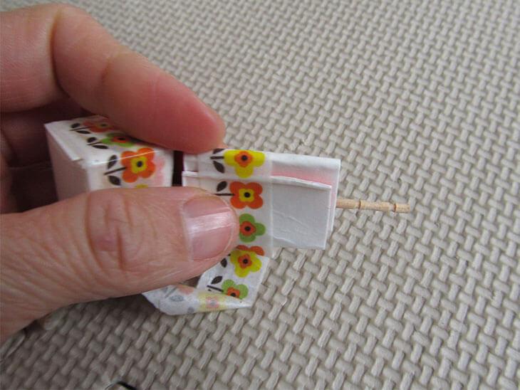吹き口部分に爪楊枝を挟み、テープで留める様子