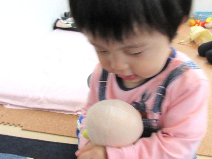 乳児がぬいぐるみに話しかける様子