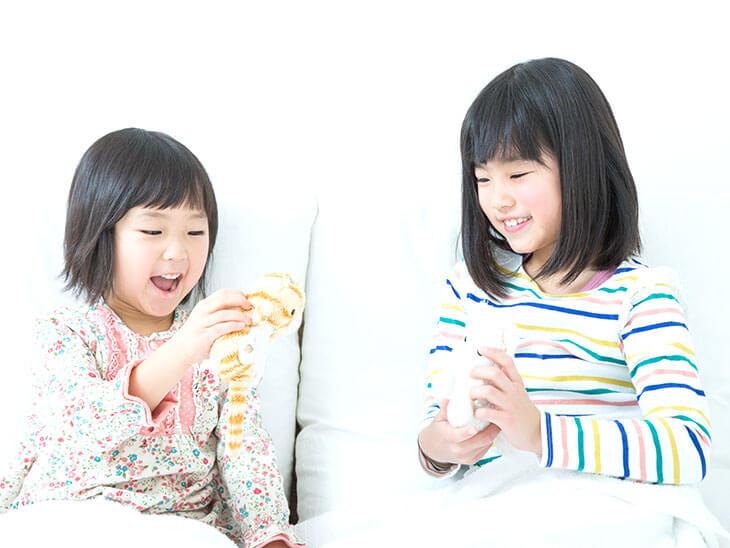 ぬいぐるみで遊ぶ姉妹
